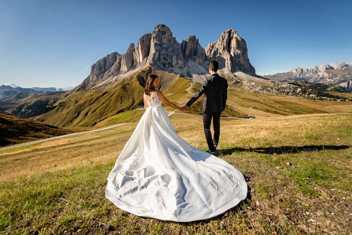 trash the dress al lago di carezza - sposi a mano guardano le montagne