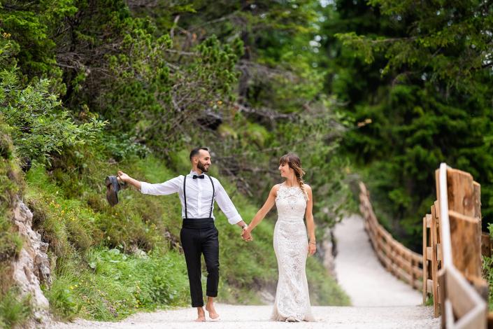 trash the dress al Lago di Braies - sposi camminano scalzi