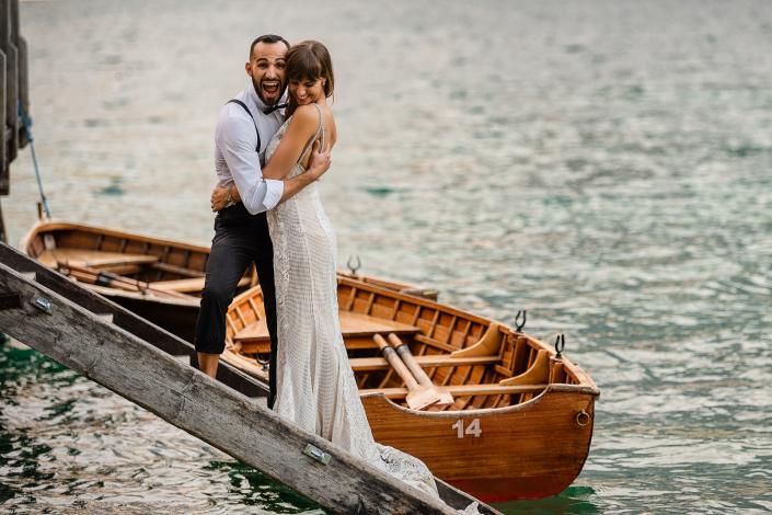 trash the dress al Lago di Braies - sposo finge di buttare in acqua la sposa