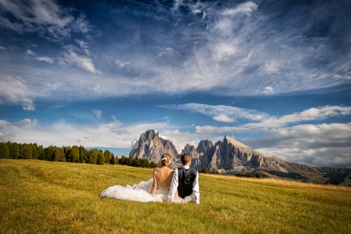 Trash the dress in Alpe di Siusi - sposi seduti guardano le montagne