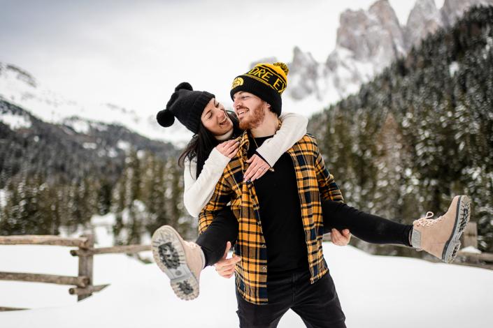 servizio fotografico di coppia in Val di Funes - lei sale in spalla al fidanzato