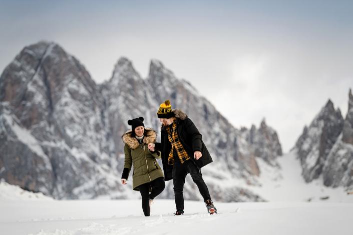 servizio fotografico di coppia in Val di Funes - coppia cammina nella neve